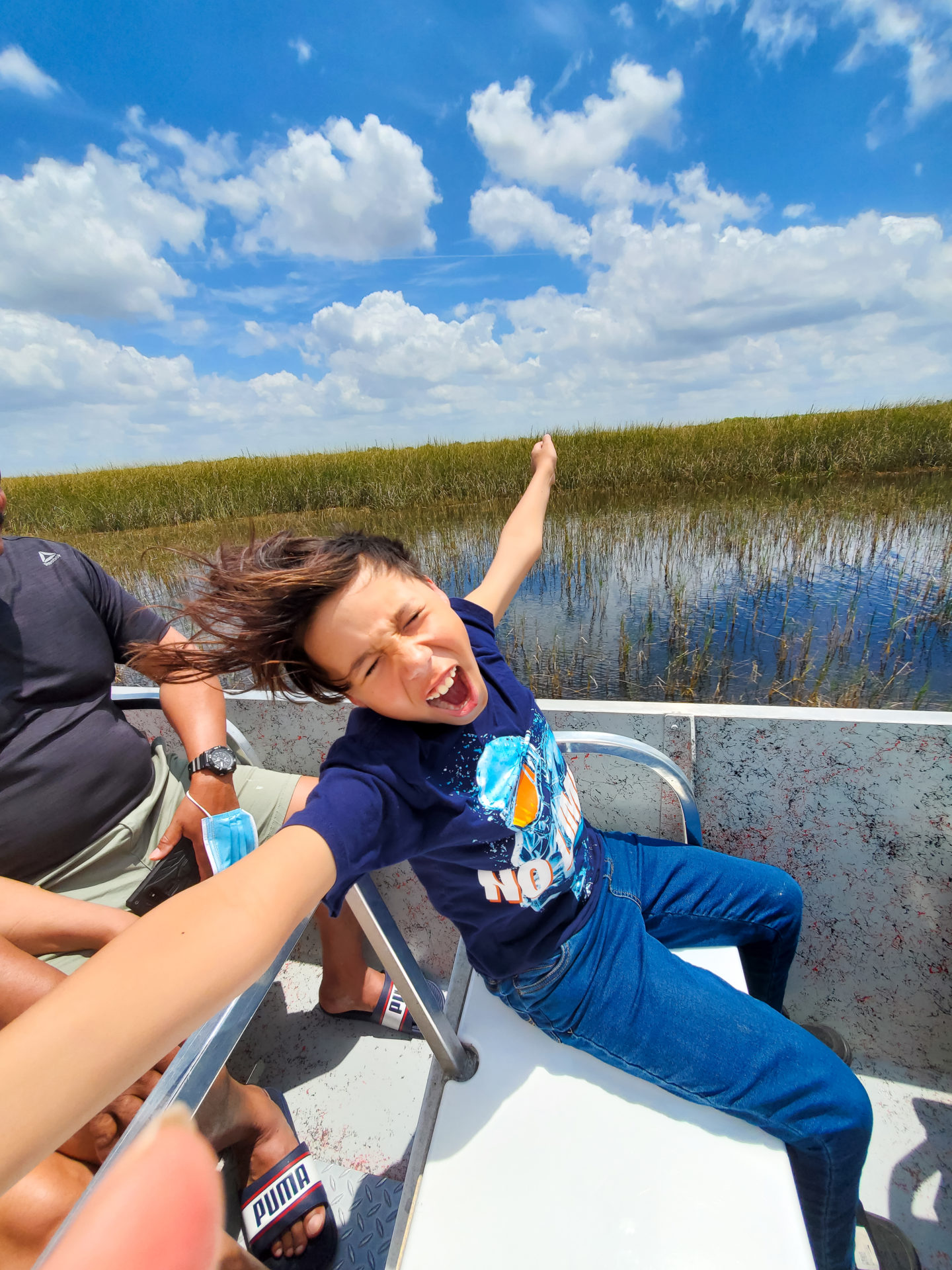 Christopher Being Happy at the Everglades. He is smiling and extending his arms.