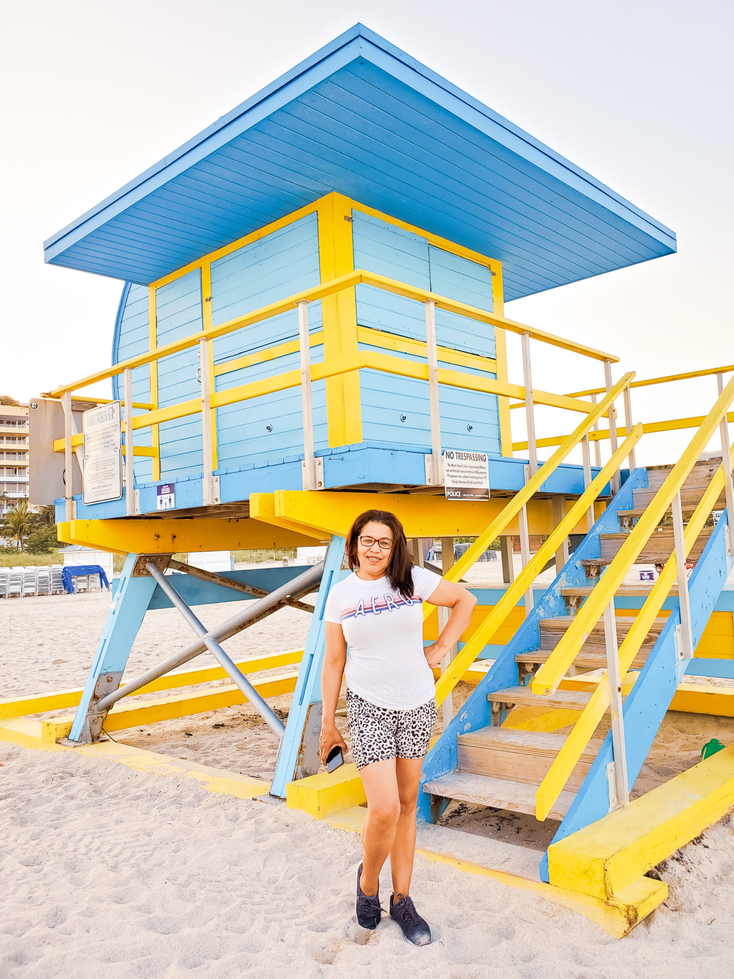 My mom Posing in front of a Lifeguard Tower.